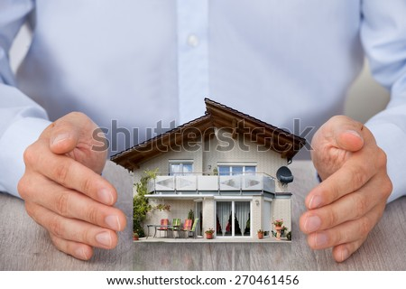 Close-up Of Man Saving Small House Model - stock photo