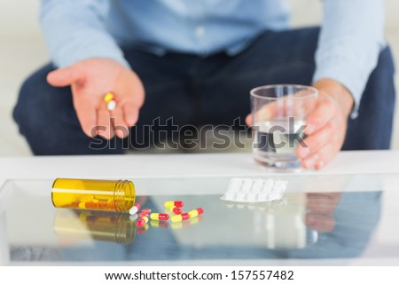Close up of man showing tablets on open hand in bright living room