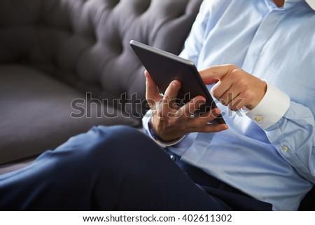Close Up Of Man Sitting On Sofa Using Digital Tablet - stock photo