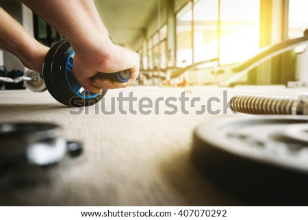 Close up of man using ABS Roller Exercise hand-roller at fitness gym vintage tone.