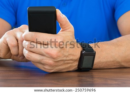 Close-up Of Man Using Cellphone And Wearing Smartwatch In Hand