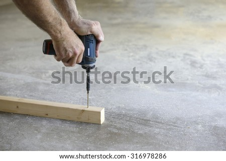 Close-up of Man Using Power Drill - stock photo