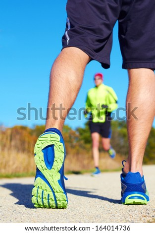 Close up of man walking on nature trail near forest preserve. Color image, copy space, male walking outside on a beautiful day in nature with a jogger running in the background blurred. Vertical