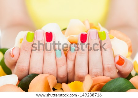Close-up Of Manicured Nail With Nail Varnish Holding Petals - stock photo