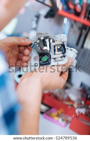 Close up of mans hands holding drone camera with chips