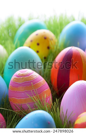 Close Up Of Many Colorful Easter Eggs On Green Grass For Easter Or Seasons Greetings Eggs In Different Colors - stock photo