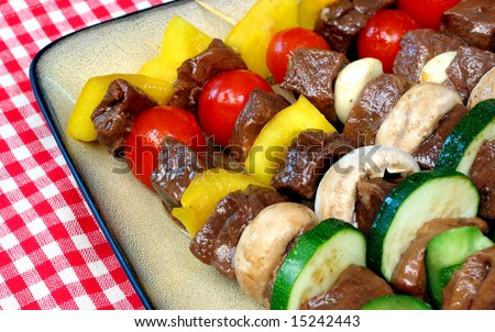 Close up of marinated meat on skewers ready to grill. - stock photo