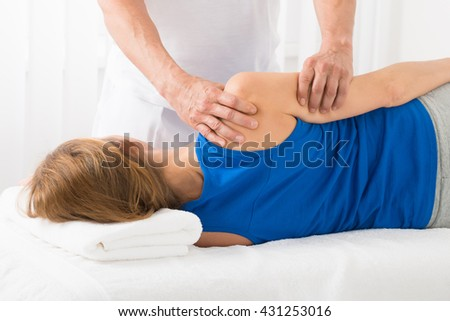 Close-up Of Masseur Doing Arm Massage On Woman In Spa - stock photo