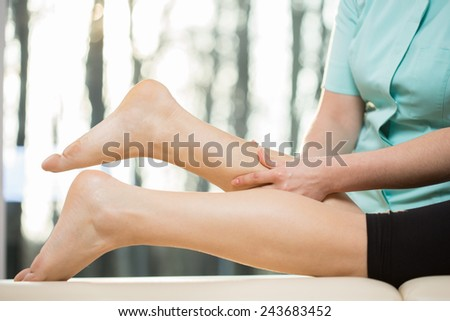 Close-up of masseur doing calf massage