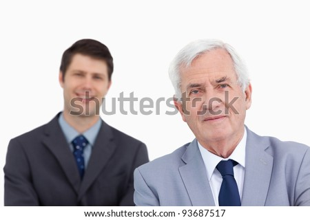 Close up of mature businessman with colleague behind him against a white background - stock photo