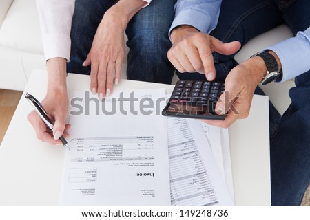 Close-up of mature couple doing finances at home - stock photo