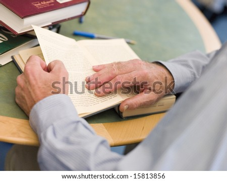Close-up of mature student's hands turning book page in library