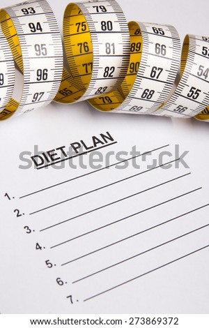 close up of measure tape on paper with diet plan - stock photo
