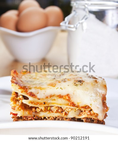 close up of meat lasagna with flour and eggs in the background - stock photo