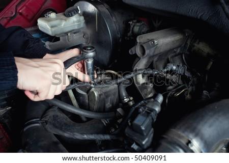 Close-up of mechanic repairing a car - stock photo