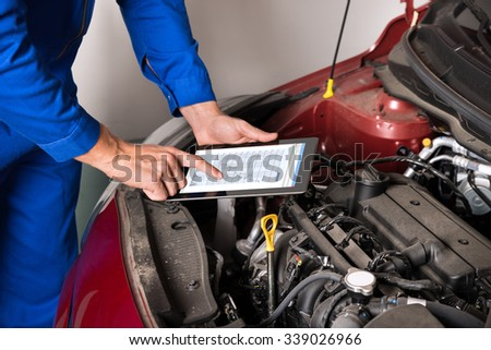 Close-up Of Mechanic Using Digital Tablet While Examining Car Engine In Garage