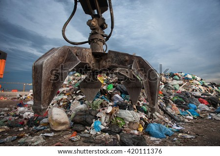 Close up of mechanical arm grabbing waste from a pile at city landfill - stock photo