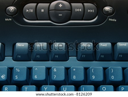 Close-up of media computer keyboard overlaid with blue