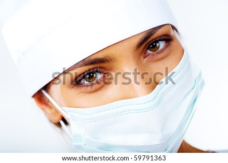 Close-up of medical nurse in mask looking at camera - stock photo