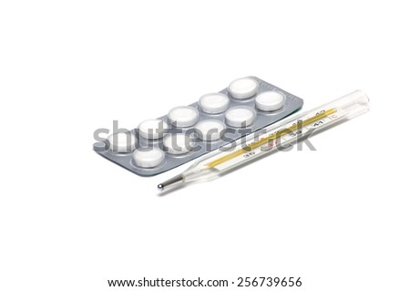 Close up of medicine white tablets in the blister and thermometer - stock photo