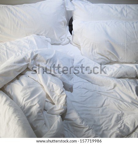 close up of messy bedding sheets and pillow - stock photo