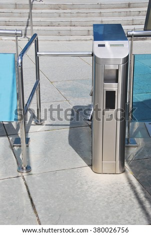 Close-up of metal closed tourniquet on cement tiled floor. Modern turnstile - stock photo