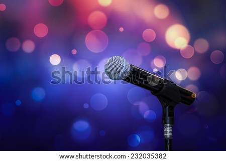 Close up of microphone in colourful background - stock photo