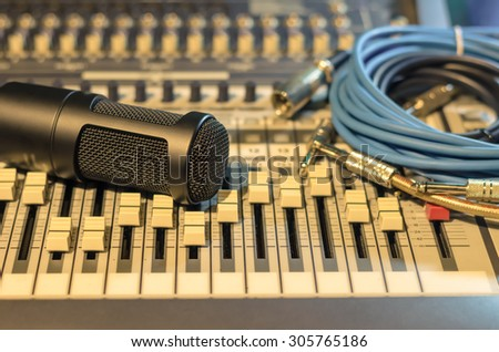 Close up of microphone with equipment on mixer, music instrument concept - stock photo