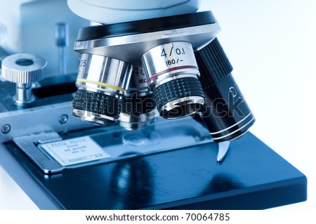 Close up of microscope lenses focused on a specimen in blue light. - stock photo