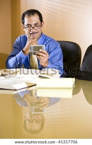 Close-up of middle-aged Hispanic businessman reading text message on mobile phone - stock photo