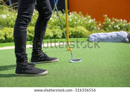 Close-up of miniature golf hole with bat and ball - stock photo