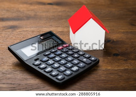 Close-up Of Miniature House With Calculator On Wooden Table - stock photo