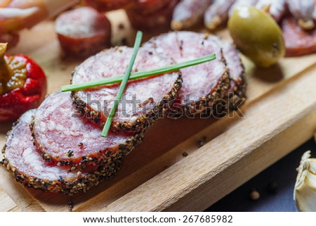 close up of mix of traditional spanish ham salami parma ham on grissini bread sticks, marinated vegetables and olives on wooden plate with rustic decor - stock photo