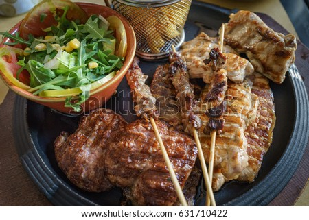 Close up of mixed grilled meat Beef, pork, poultry with grilled garlic, chili pepper and vegetable salad.