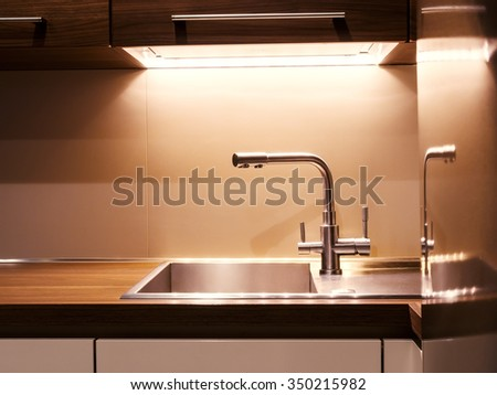Close-up of modern kitchen faucet and sink - stock photo