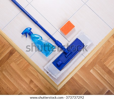 Close up of mopping cleaning tools on tiled floor - stock photo