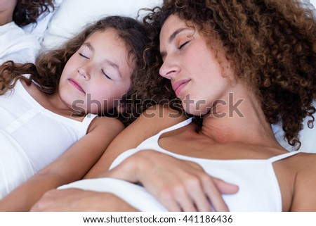 Close-up of mother and daughter sleeping together on bed - stock photo