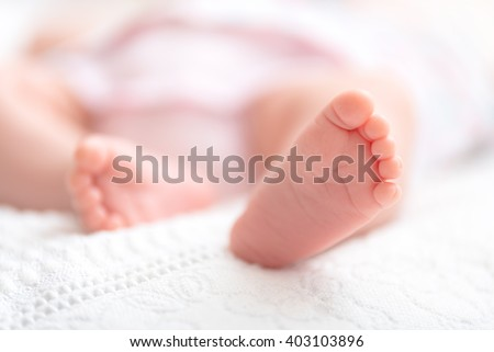 Close-up of mother hands holding tiny baby feet - stock photo