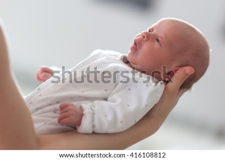 Close up of mother holding cute baby girl in her hands,