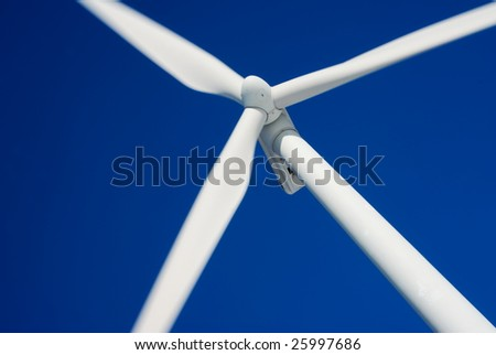 Close-up of moving wind turbine with deep blue sky - stock photo