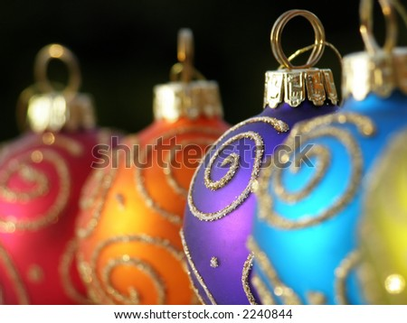 Close-up of multi colored Christmas baubles in a row with swirl decoration in gold - stock photo