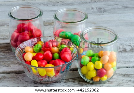 Close-up of multicolored candies in glass bowl and jars on wooden table - stock photo