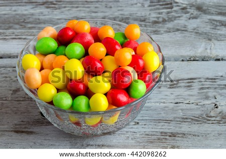 Close-up of multicolored candies in glass bowl on wooden table in daylight - stock photo