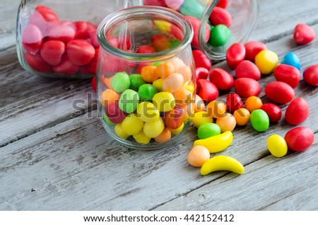 Close-up of multicolored sweets and caramels on table and in glass jar - stock photo
