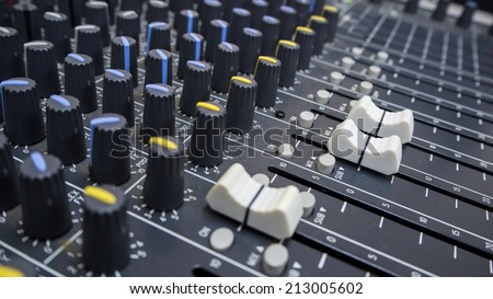 Close-up of music controls buttons of studio mixer - stock photo