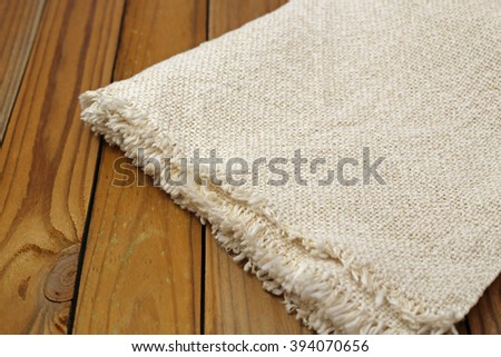 Close up of natural white linen napkin on brown wooden rustic textured surfaces background - stock photo