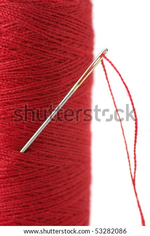 Close-up of needle with thread in red reel on white background.