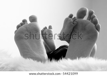 Close up of newborn and mother feet - stock photo
