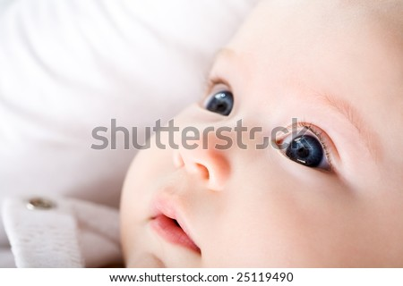 Close-up of newborn baby with blue eyes looking upwards surprisingly - stock photo