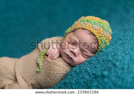 Close up of newborn sleeping in a green and yellow knit hat - stock photo